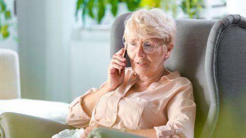 Eine Frau mittleren Alters lehnt in einem großen Sessel. Mit der rechten Hand hält sie sich ein mobiles Telefon ans Ohr.