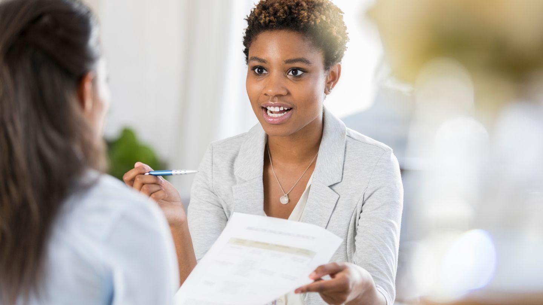 Informationsangebote für Patienten und Ratsuchende: Eine Frau hält ein Dokument in der Hand und zeigt es einer anderen Frau, die gegenübersitzt. In der anderen Hand hält sie einen Kugelschreiber.