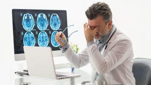 Behandlungsfehler: Ein Arzt sitzt vor einem Laptop. Daneben steht ein großer Bildschirm, der Bilder eines gescannten Schädels zeigt. Der Arzt presst sich zwei Finger an die Augen und verzieht den Mund, sodass zusammengepresste Zähne sichtbar sind.