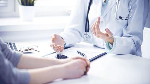 Eine Ärztin und eine Patientin sitzen an einem Tisch. Sprechen miteinander. Die Patientin holt sich eine Zweitmeinung ein. Vor der Ärztin auf dem Tisch liegt ein ausgedrucktes Dokument aus einer Patientenakte.