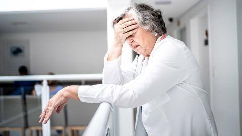 Spannungskopfschmerzen: Eine ältere Frau lehnt an einem Geländer und fasst sich mit einer Hand an die Stirn. Die Frau wirkt erschöpft.