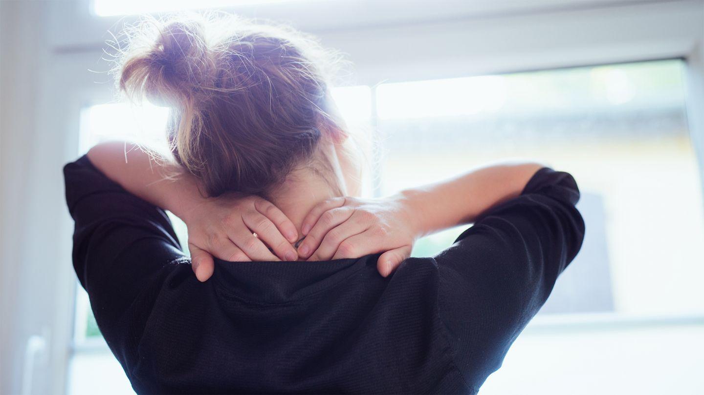 Stress: Eine Frau mit hochgebundenen Haaren steht vor dem Fenster und streckt die Arme nach oben und drückt mit den Händen gegen ihren verspannten Nacken. Sie hält den Kopf dabei schräg in Richtung Schulter, um ihren Nacken zu dehnen.
