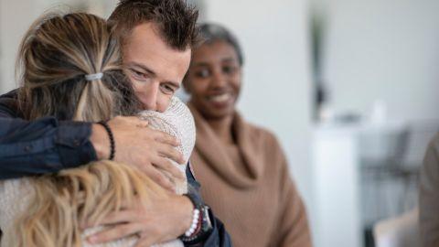 Ein Mann und eine Frau umarmen sich. Sie sitzen in einem Zimmer, offenbar in ein einer Runde mir mehreren Patienten. Im Hintergrund sitzt eine Frau, die zu beiden hinüberschaut und lächelt.