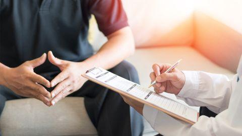 Syphilis: Ein Mann sitzt auf einer Couch, seine Hände Formen eine Raute. Schräg vor ihm sitzt ein Arzt, der ein Klemmbrett und einen Kugelschreiber in den Händen hält.