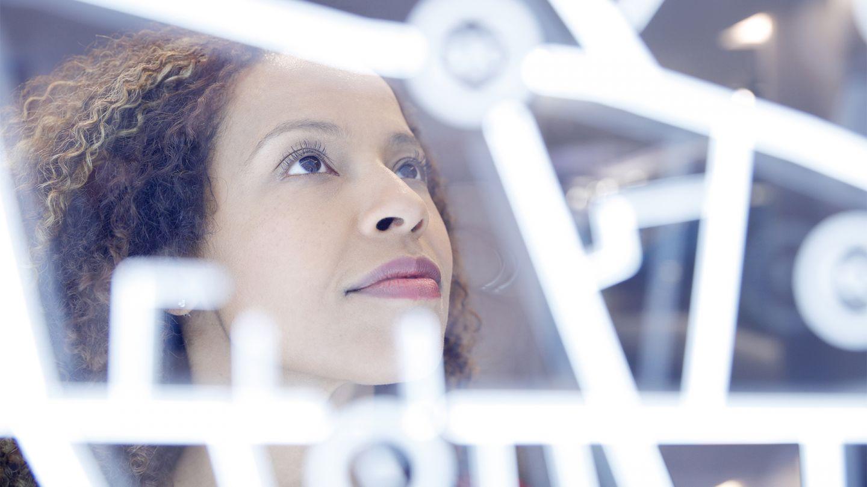 Telematikinfrastruktur: Eine Porträtaufnahme einer Frau, die auf ein digitales medizinisches Interface schaut.