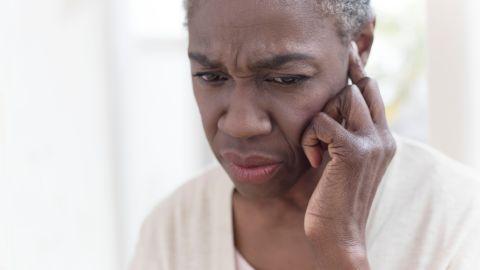 Tinnitus: Eine Frau fasst sich mit einem Finger ans Ohr und schaut skeptisch.
