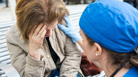 Transitorische ischämische Attacke (TIA): Eine Frau sitzt auf einer Bank, fasst sich mit einer Hand an die Stirn und neigt ihren Kopf leicht nach unten. Eine Arzthelferin kniet vor der Frau und fasst ihr mit der rechten Hand an die linke Schulter.