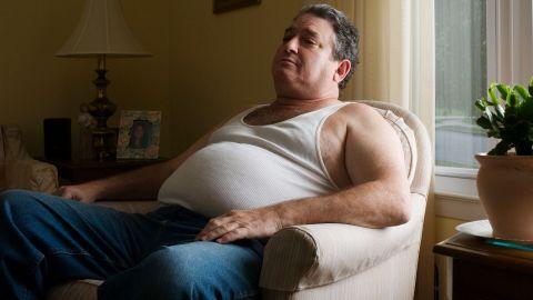 Ein übergewichtiger Mann sitzt in einem Sessel. Unter dem Feinrippunterhemd, das der Mann trägt, ist ein dicker Bauchansatz zu erkennen.