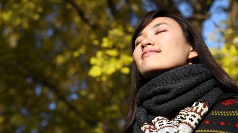 Vitamin D Mangel: Eine junge Frau befindet sich im Wald, Sonne strahlt auf ihr Gesicht. Ihre Augen sind geschlossen, sie wirkt entspannt.
