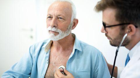 Vorhofflimmern: Ein älterer Herr wird von einem Arzt mit einem Stethoskop am Herz untersucht.