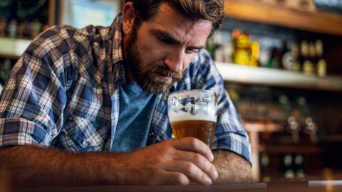 Alkohol: Ein Mann sitzt alleine in einer Bar, lehnt sich mit beiden Armen auf den hölzernen Tresen, hält ein Bierglas in der Hand und schaut in den Glas.