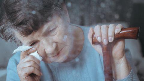 Alzheimer-Demenz: Eine Frau mit Gehstock hält ein Taschentuch an ihr Auge und blickt nach unten.