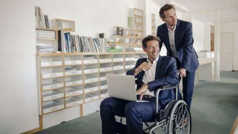 Betriebliche Gesundheitsförderung: Ein Herr im Anzug schiebt einen Arbeitskollegen, welcher grinsend in einem Rollstuhl sitzt und einen Laptop auf dem Schoß hat, durch das Büro. Beide Männer schauen nach links.