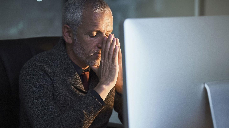 Burn-out: Ein Mann sitzt mit geschlossenen Augen vor einem Bildschirm und fasst sich an die Stirn.
