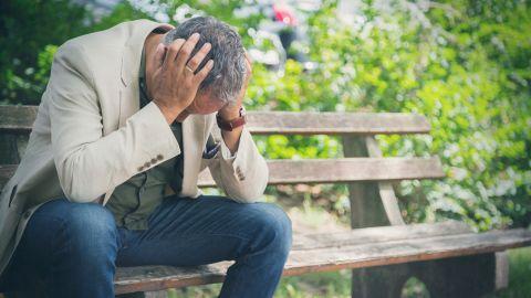 Cluster-Kopfschmerzen: Eine Mann sitzt auf einer Parkbank und versenkt den Kopf und fasst sich mit beiden Händen an den die Schläfen.