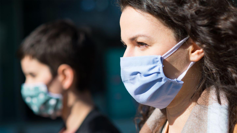 Eine junge Frau steht in einem Bus. Sie trägt einen Mund-Nase-Schutz und hält sich die Hand ans Gesicht. Sie wirkt erschöpft.
