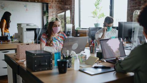 Zwei Frauen und ein Mann sitzen gemeinsam an einem großen Schreibtisch und arbeiten. Sie alle tragen einen Mund-Nase-Schutz und sind durch Plexiglasscheiben voneinander getrennt.