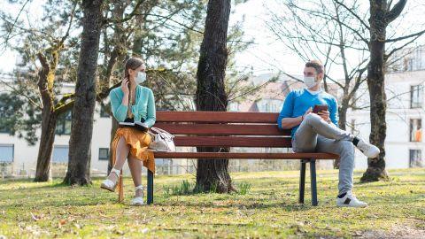 Ein Mann und eine Frau sitzen auf einer Parkbank und gucken sich an. Zwischen ihnen ist ungefähr 1,5 Meter Abstand. Beide tragen einen Mundschutz.