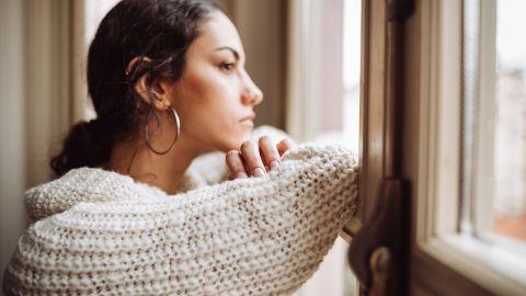 Depression: Eine Frau blickt gedankenverloren aus einem Wohnungsfenster.