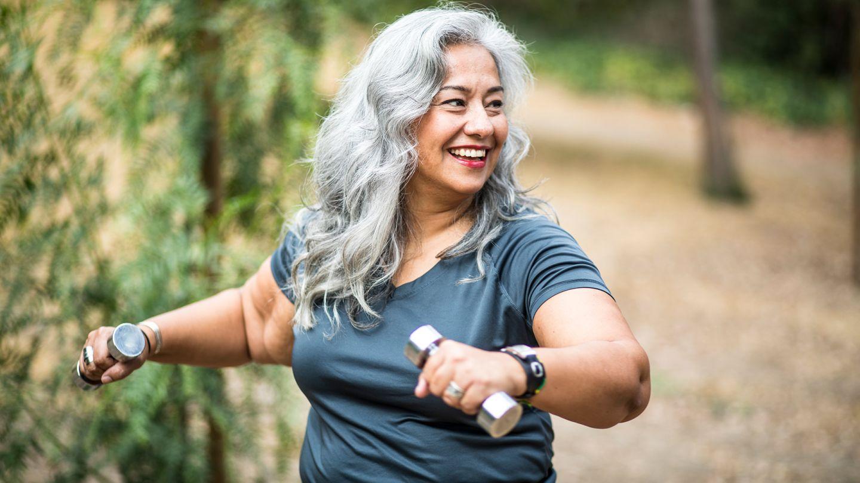 Diabetes Typ 2: Eine Frau hält Hanteln in beiden Händen, ist sportlich aktiv und lächelt.