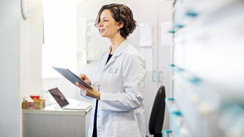 Telemonitoring: Eine Ärztin steht in einer Praxis. Sie hält ein Tablet in der linken Hand, ihre rechte Hand berührt den Bildschirm des mobilen Gerätes. Im Hintergrund steht unter anderem ein Laptop auf einem Tisch.