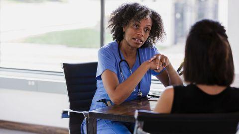 Eierstockkrebs: Eine Ärztin und eine Patientin sitzen an einem Tisch. Die Ärztin spricht mit der Patientin.