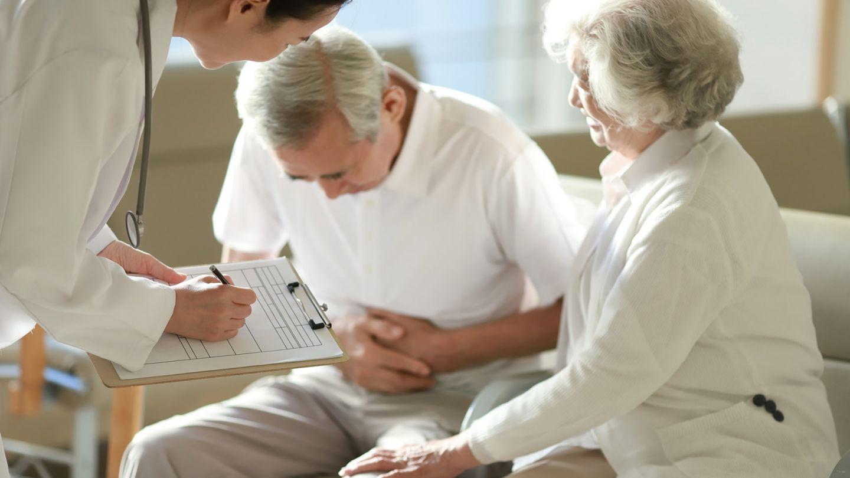 Gallensteine: Eine älterer Mann sitzt auf einer Couch, hat seinen Oberkörper nach vorne gebeugt und presst beide Hände an den Bauch. Eine Frau sitzt neben ihm und berührt mit einer Hand sein linkes Bein. Vor ihnen steht ein Arzt, der sich Notizen macht.