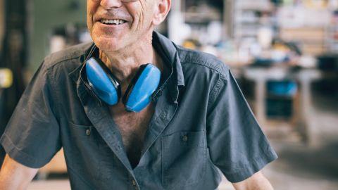 Ein älterer Mann trägt Arbeitskleidung, unter anderem einen Hörschutz. Der Mann lächelt.