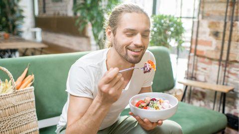 Ein junger Mann sitzt auf einem Sofa und isst einen Salat. Er lächelt dabei. Hinter ihm steht auf dem Sofa ein Korb mit Gemüse.