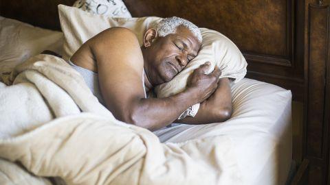 Gesunder Schlaf im Alter: Ein älterer Mann liegt auf der Seite im Bett und schläft. Mit gebeugtem Arm klemmt er sich sein Kissen zwischen Kopf und Arm.