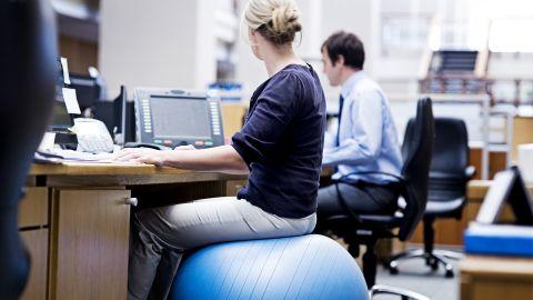 Gesundheit am Arbeitsplatz: Eine Frau sitzt auf einem Gymnastikball am Schreibtisch und schaut nach rechts zu einem Display.