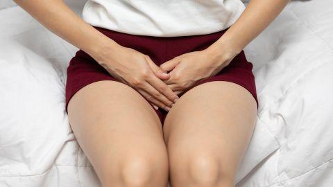 Harnwegsinfektion Zystitis: Eine junge Frau sitzt auf einem Bett und fasst sich mit beiden Händen an den Schritt.