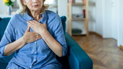 Eine Frau sitzt auf einem Sessel in einem Zimmer. Sie fasst sich mit beiden Händen zwischen die Brust und den Hals. Ihr Mund ist leicht geöffnet.
