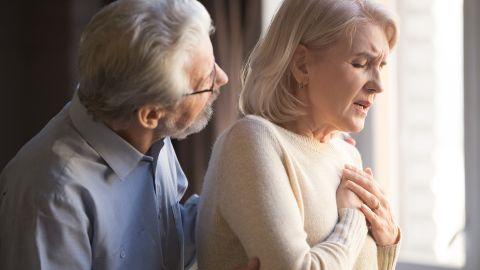 Herzrhythmus-Störung: Eine Frau fasst sich mit beiden Händen an den Brustkorb.