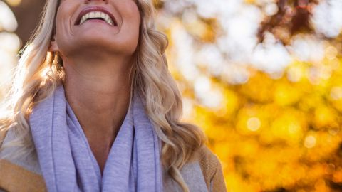 Glücksgefühle durch Hormone: Eine Frau, die ein Handtuch um den Hals trägt, legt ihren Kopf in den Nacken und lächelt. Im Hintergrund Laub, Äste und Bäume.
