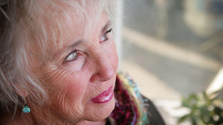 Grauer Star (Katarakt): Eine ältere Frau mit grünblauen Augen schaut in die Ferne.