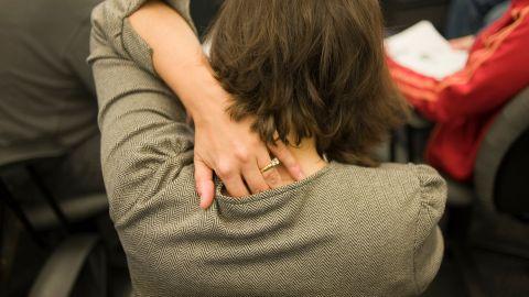 Kleienpilzflechte: Eine Frau steht mit dem Rücken zugewandt in einer Menschenmenge und greift sich mit der linken Hand an ihren Nacken.