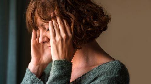 Migräne: Eine Frau fasst sich mit beiden Händen an den Kopf.