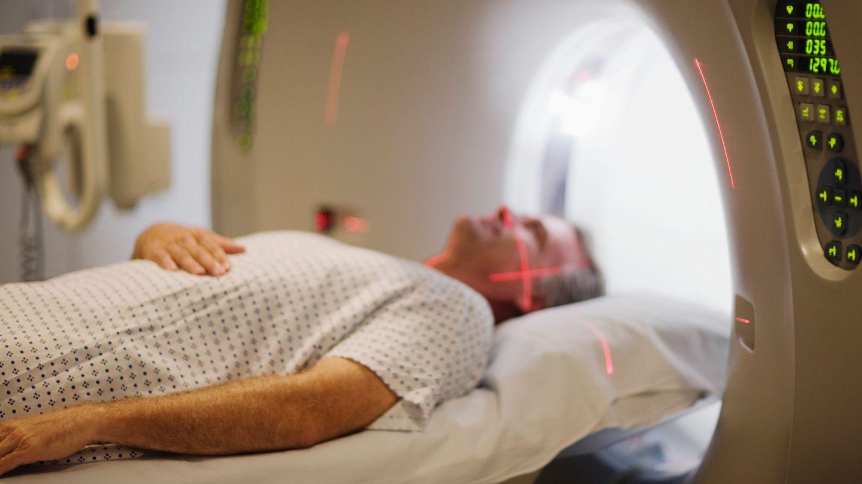 Multiples Myelom: Ein Mann liegt in einer MRT-Röhre. Über seinem Gesicht verlaufen zwei rote Laser.