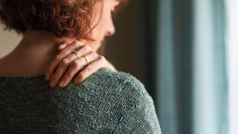 Eine Frau fasst sich mit der linken Hand an die rechte Schulter nahe des Halses.