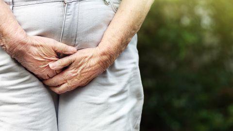 Eine ältere Frau steht in einer Grünanlage und presst ihre Hände gegen den Unterleib. Ihre Armhaltung wirkt angespannt.