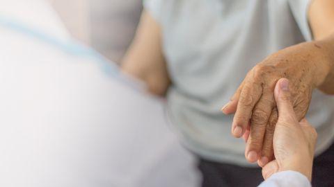 Parkinson: Eine Frau in einem weißen Kittel, offenbar eine Pflegerin, nimmt eine ältere Frau an beide Hände.