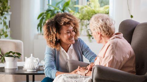 Pflegebedürftig: Eine ältere Frau sitzt in einem Sessel. Neben ihr kniet eine jüngere Frau. Sie hält mit beiden Händen eine Hand der älteren Frau, schaut sie an und und lächelt. Im Hintergrund: Zimmerpflanzen.
