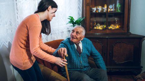 Ein alter Herr möchte aus seinem Wohnzimmersessel aufstehen, er hat einen Gehstock zur Hilfe. Eine junge Frau hilft ihm bei dem Aufstehen und greift ihm unter den Arm als Stütze.