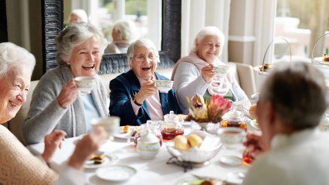 Pflege-WGs – Leben in ambulant betreuten Wohngruppen: Fünf Seniorinnen sitzen an einem Esstisch, auf dem unter anderem Schälchen mit Brötchen und Marmelade stehen. Alle Frauen haben eine Tasse in der Hand, heben sie an und prosten sich zu.