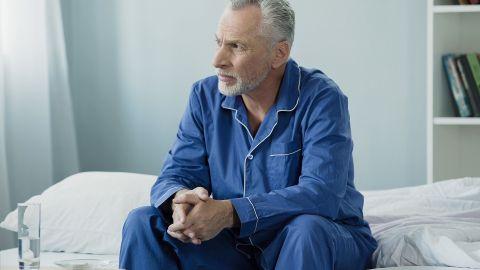 Gutartige Prostatavergrößerung (Prostatahyperplasie): Ein Mann mittleren Alters sitzt am Rand eines Krankenbettes. Er hat seine Hände ineinander gefaltet und schaut nachdenklich in Richtung Fenster.