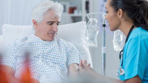Prostatakrebs: Ein älterer Mann sitzt in einem Krankenhausbett. Er schaut nach unten, ihm gegenüber sitzt eine Krankenschwester. Sie schaut ihn an und entnimmt ihm Blut.