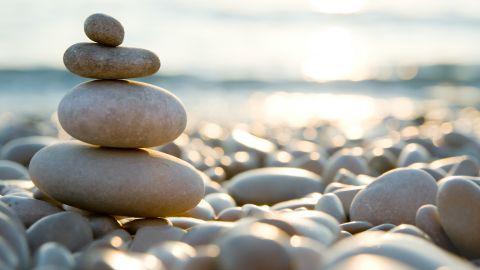 Vier Kieselsteine in unterschiedlicher Größen, die aufeinander gestapelt sind, wahrscheinlich an einem Strand. Im Hintergrund eine untergehende Sonne, deren Strahlen in Wasser reflektiert werden.