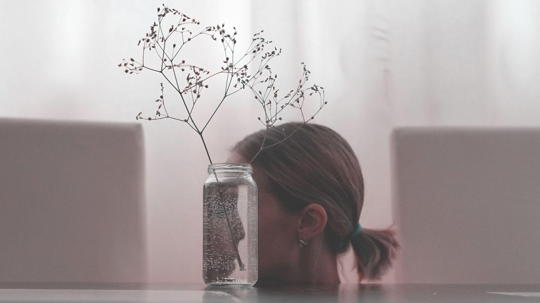 Schizophrenie: Abgebildet ist das Profil einer jungen Frau. Ihr Gesicht ist hinter einer durchsichtigen Blumenvase verborgen. Das Gesicht der Frau spiegelt sich verkehrt herum im Glas.