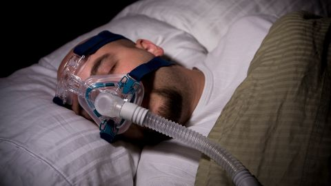 Schlafapnoe: Ein Mann liegt in einem Bett und trägt eine Beatmungsmaske. Er scheint zu schlafen.